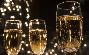 3 champagne glasses with sparkles in the background