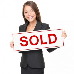woman holding a sold sign