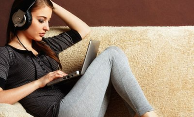 girl sitting on couch studying and listening to music