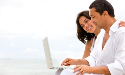 happy beach couple on a laptop during vacation