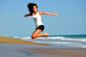 girl jumping near ocean
