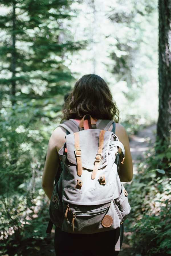 Girl with backpack in the woods