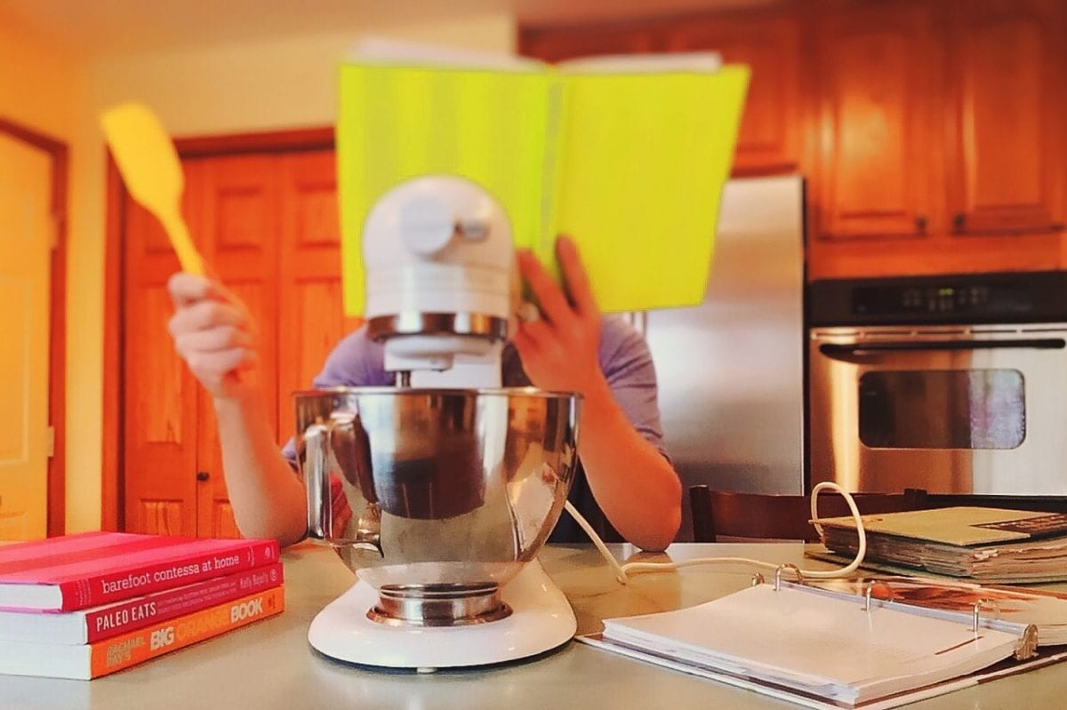 person holding cookbook and spatula with mixer