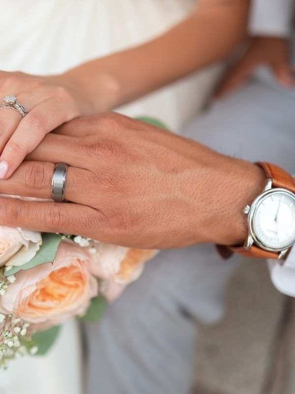 bride and groom holding hands on bouquet