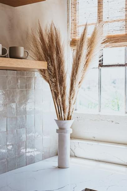 Place pampas grass in a small vase on top of kitchen countertop