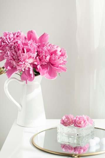 Pink peony flower arrangement in white ceramic vase