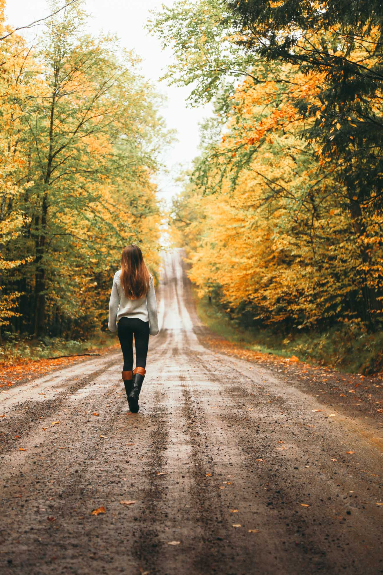 girl walking down dirt road with fall colors in wisconsin