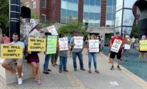 """About a dozen people opposed to a mask ordinance in Columbia are seen protesting outside Columbia City Hall, carrying signs that say """"we will not comply"""" and 'freedom and force cannot coexist."""""""