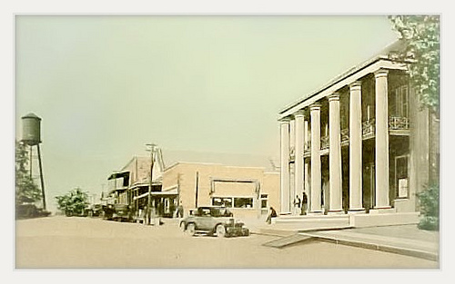 Woodville- the town square and the West Felciana Railroad Office Building- colrized post card view from the 1930s
