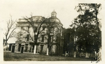 "J.F. Laist, 1915. View of north side of Old Capitol Building, three story stone, plaster, brick building in decayed condition, sign in front says ""Danger Keep Out,"" grounds, trees, fences, ticket booths. MDAH Accession PI/STR/C36 /Box 20 Folder 95"