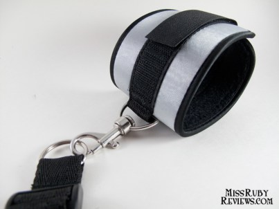 Cuffs hook onto rings on the restraint harness