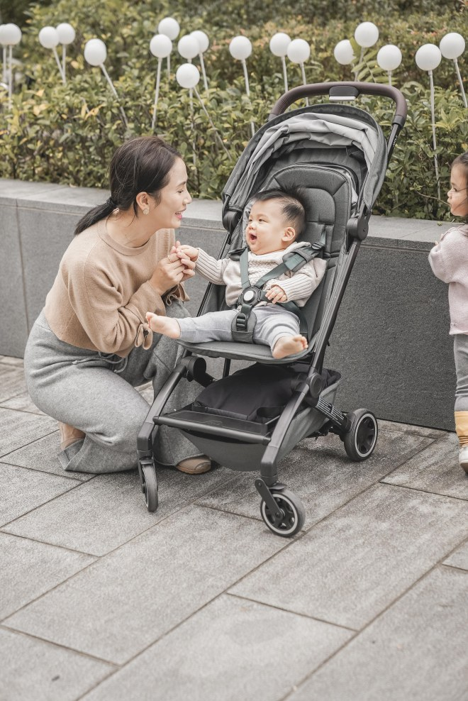 A person pushing a baby in a stroller  Description automatically generated