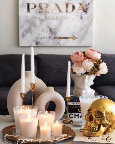 H&M Circle Vases, Gold Skull, Nest Candles, H&M Face Vase with flowers, Prada Marfa sign, gray couch, marble table