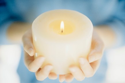 Hands Holding a Lit Candle