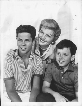 """(Barbara Billingsley, Tony Dow and Jerry Mathers, """"Leave It to Beaver"""" -- public domain) On Air: Thursdays, 9-9:30 PM, EDT. """"Beaver"""" Trio Barbara Billingsley, who stars as Mrs. Cleaver, poses with television sons Tony Dow (Wally) left, and Jerry Mathers (Beaver) on the set of ABC-TV's """"Leave It to Beaver"""" Thursdays, 9-9:30 PM, EDT."""