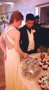 Bride and groom cutting the main cake, with cupcakes stacked around it.
