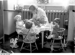 mother with daughter's dolls, having a tea party