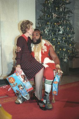 First Lady Nancy Reagan sitting on Mr. T's lap and kissing him on the forehead.
