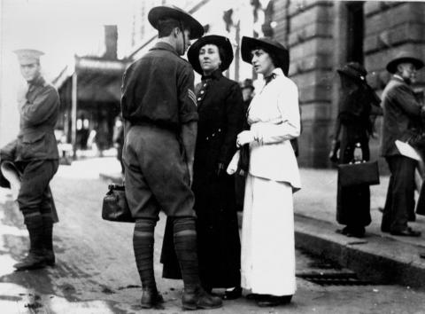 WWI soldier talking to two women