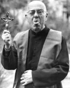 Padre Amorth impugna un crocifisso mostrando la lingua in segno di scherno.
