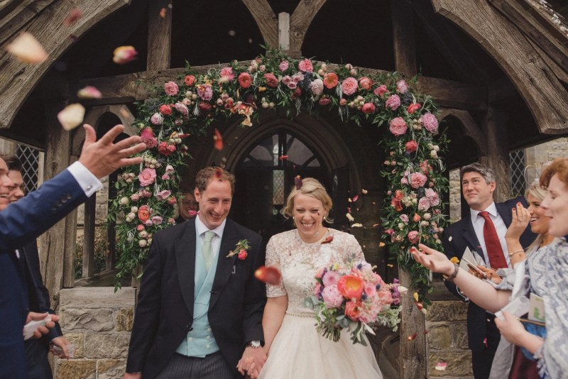 Throwing confetti at the bride and groom outside the church