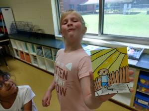 Girl smirking and showing her cartoon drawing of a boy walking on a sunny day