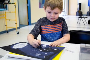 Boy drawing an outer space picture