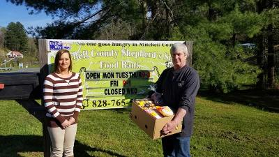 Tabitha Callahan and Larry Davis pose with food boxes at the Shepherd's Staff sign