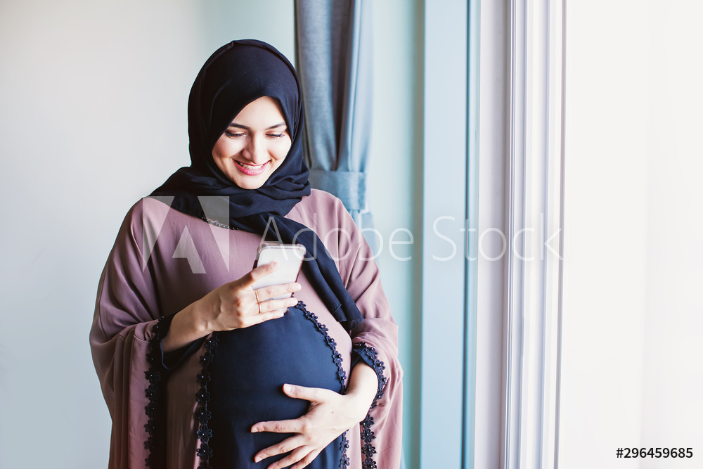Young pregnant arab woman in hijab using her mobile phone to send message. Tetap Stylish Berhijab Ketika Hamil.