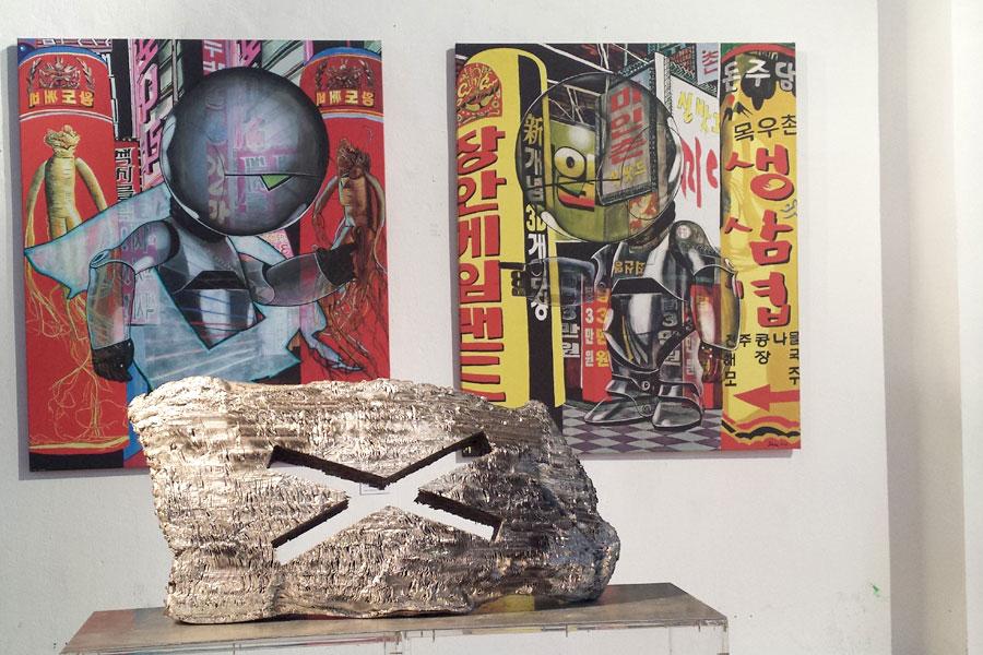 """im Vordergrund: ein Werk von Gottfried Höllwarth (""""Objekt Serie X"""") und im Hintergrund zwei Bilder von Isolde Joham (""""Marvin in Seoul I und II"""")"""