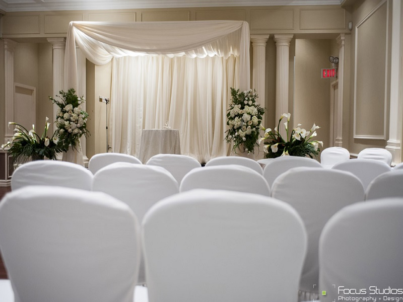 A Greek-style draped chuppah is the center of attention at this indoor wedding