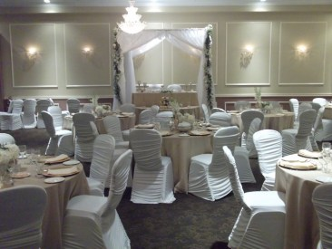 Indoor all white wedding reception with two-person dais