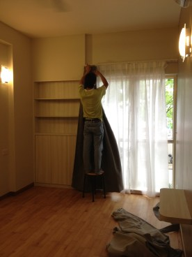 Installer hanging up curtains in the master bedroom