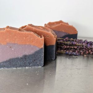 three bars of organic handmade soap lavender sunset three color layers made with pink clay, rosehip powder and indigo scented with lavender and orange essential oils next to lavender buds
