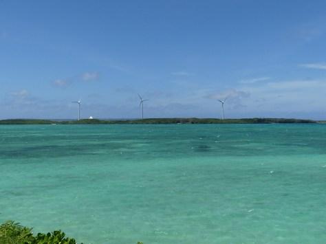 エメラルドグリーンの海沿いに風力発電3基