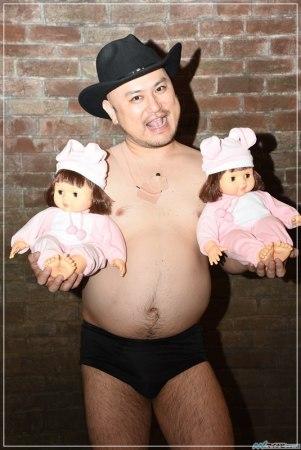 ハリウッドザコシショウが双子の人形を抱えている画像