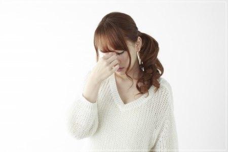 頭痛がして眉間に指をあてる女性学生の画像