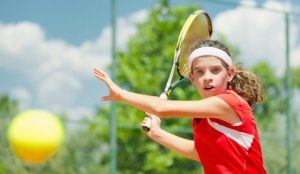 Young tennis champion hitting forehand, toned image