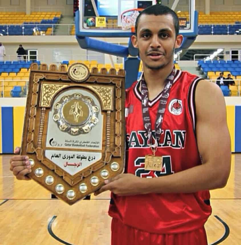 red jersey number 24 Mizo Amin holding qatar's Leauge trophy