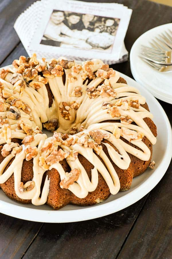Napkins, plates, and forks surround chai Bundt cake that is waiting to be sliced and served. | mjbakesalot.com