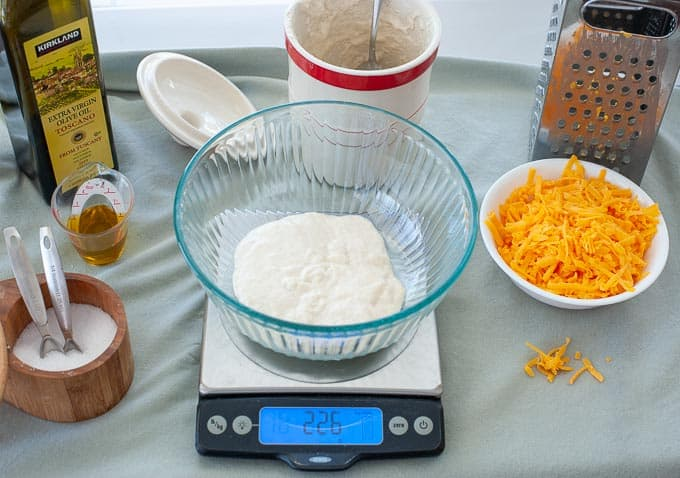 The starter for easy cheesy sourdough crackers is added to the mixing bowl.