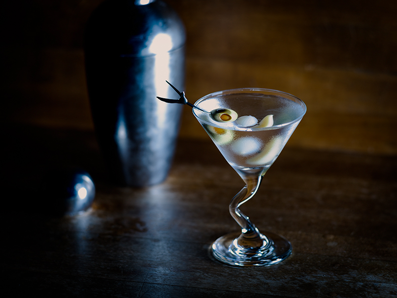 martini with olive cocktail onion and garlic shaker behind moody lighting