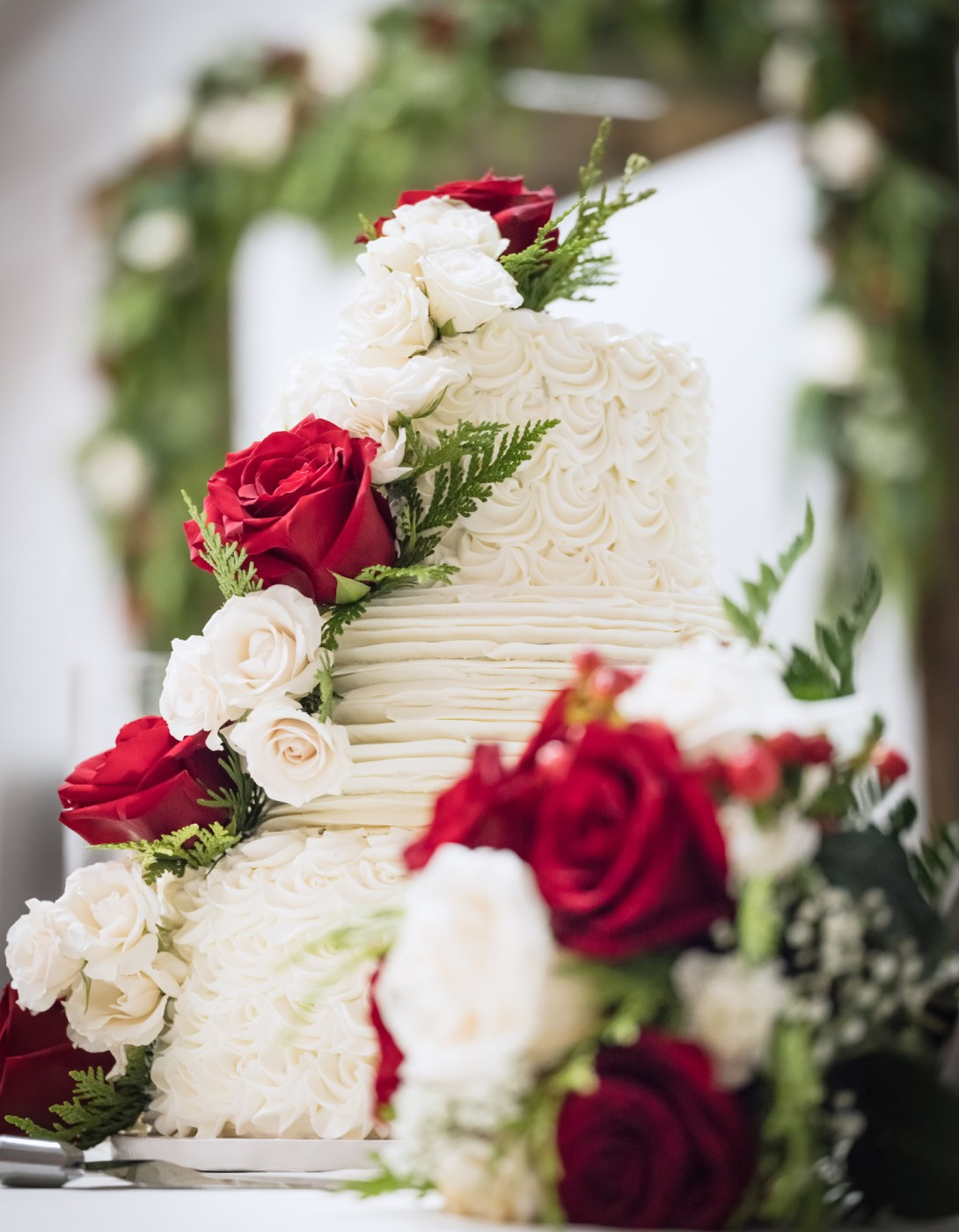 Wedding Cake Red Roses Greenery Shallow Depth of Field