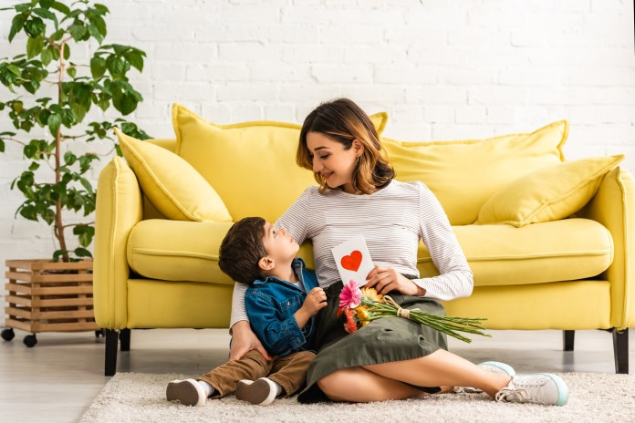 smiling woman looking at adorable son while sitting on floor with mothers day card and flowers