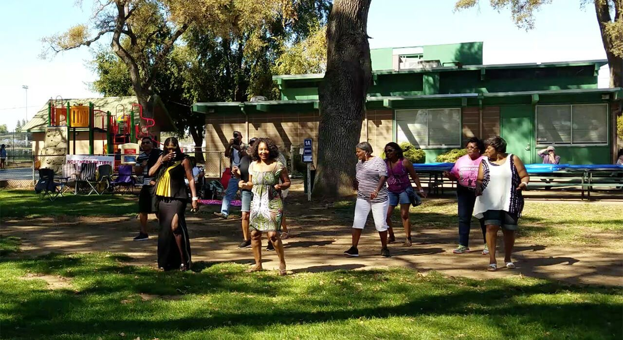 group of people dancing under a large shade tree