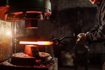 muscular forger man with beard using hydraulic press for steel arms manufacture ...