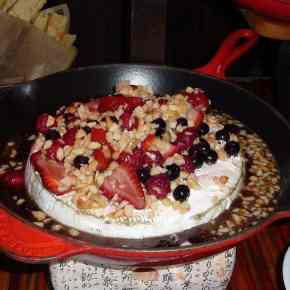 Round of brie covered with honey, fruit and nuts.