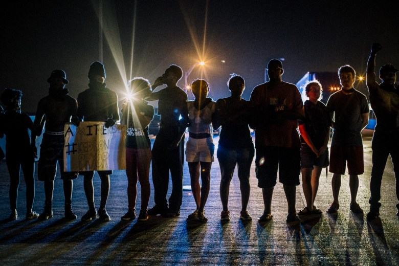 Protesters stand shoulder to shoulder along road at night