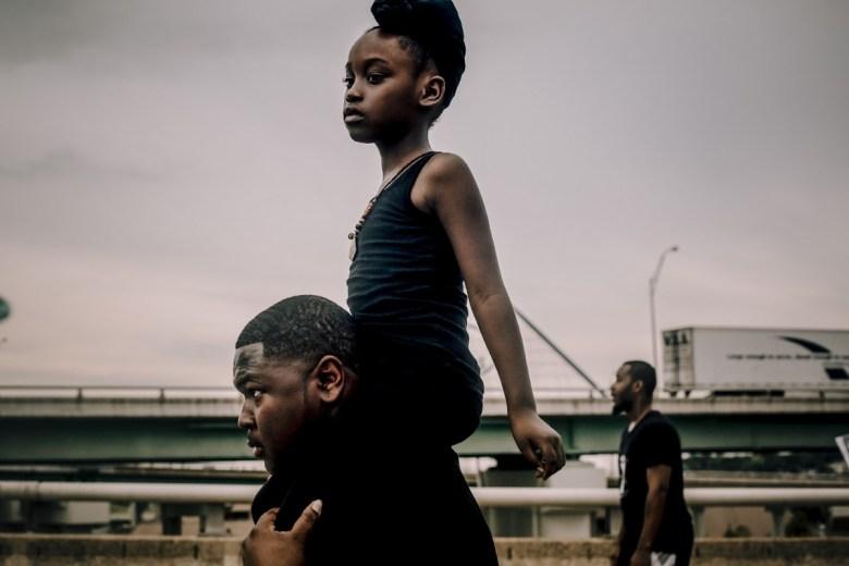 Young Black girl rides on man's shoulders across Hernando DeSoto Bridge