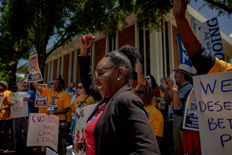 Margaret Cook raises a fist in the air during a rally in 2019 demanding a living wage from the University of Memphis.